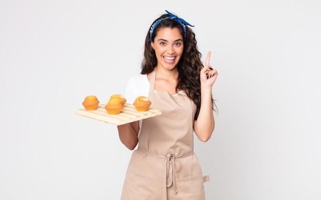 Mulher bonita se sentindo como um gênio feliz e animado depois de perceber uma ideia e segurando uma bandeja de muffins