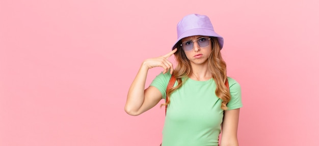 Mulher bonita se sentindo confusa e intrigada, mostrando que você é louco. conceito de verão Foto Premium