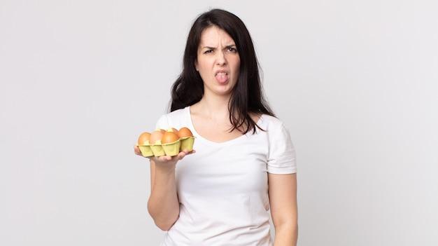 Mulher bonita se sentindo enojada e irritada, com a língua de fora e segurando uma caixa de ovos