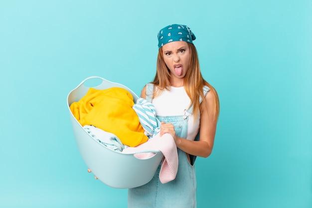 Mulher bonita se sentindo enojada e irritada com a língua de fora segurando um cesto de roupa suja