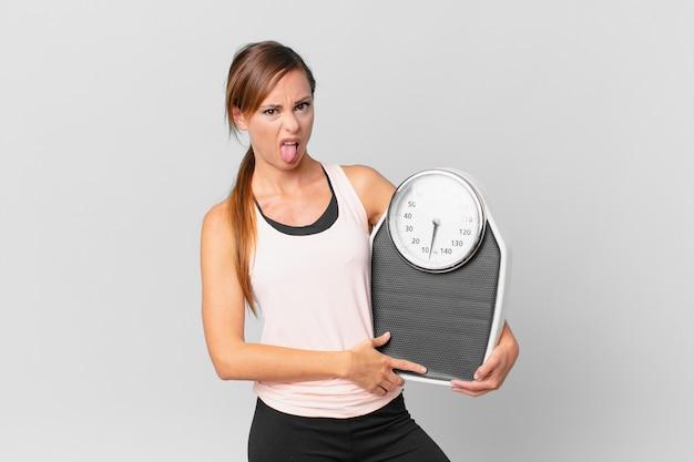 Mulher bonita se sentindo enojada e irritada e com a língua de fora. conceito de dieta