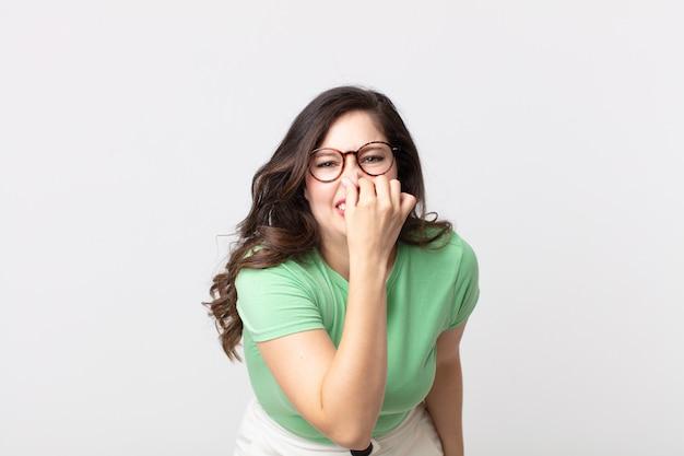 Mulher bonita se sentindo enojada, segurando o nariz para evitar cheirar um fedor desagradável e desagradável