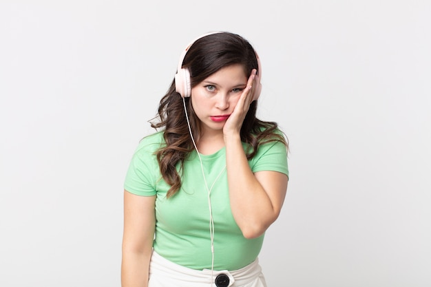 Mulher bonita se sentindo entediada, frustrada e com sono depois de ouvir música cansativa com fones de ouvido