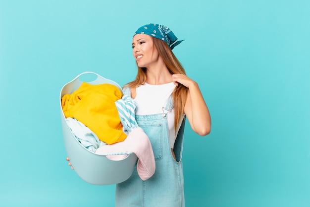 Mulher bonita se sentindo estressada, ansiosa, cansada e frustrada segurando um cesto de roupa suja