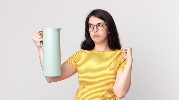 Mulher bonita se sentindo estressada, ansiosa, cansada e frustrada segurando uma garrafa térmica de café