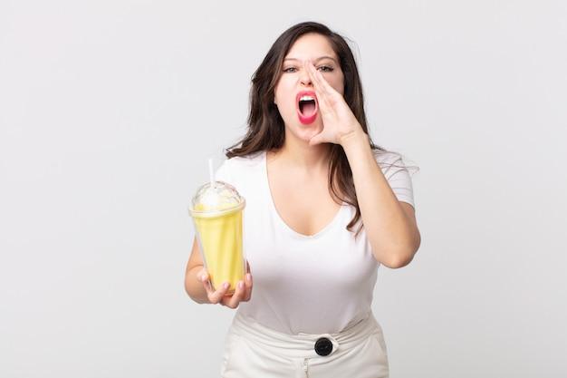 Mulher bonita se sentindo feliz, dando um grande grito com as mãos perto da boca e segurando um milkshake de baunilha