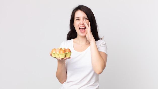 Mulher bonita se sentindo feliz, dando um grande grito com as mãos perto da boca e segurando uma caixa de ovos