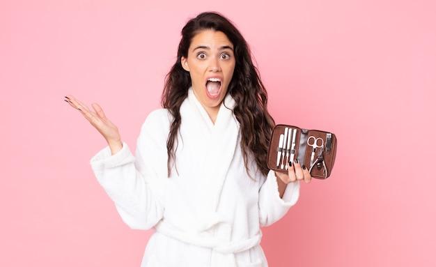 Mulher bonita se sentindo feliz e surpresa com algo inacreditável e segurando uma bolsa de maquiagem com ferramentas de unhas