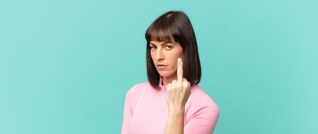 Mulher bonita se sentindo irritada, irritada, rebelde e agressiva, sacudindo o dedo do meio, lutando de volta
