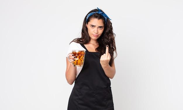 Mulher bonita se sentindo irritada, irritada, rebelde e agressiva segurando um copo de cerveja
