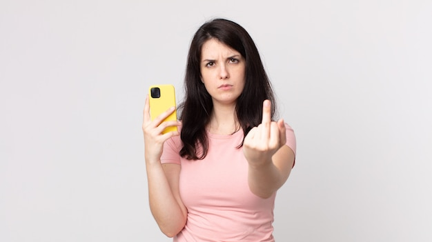 Mulher bonita se sentindo irritada, irritada, rebelde e agressiva usando um telefone inteligente