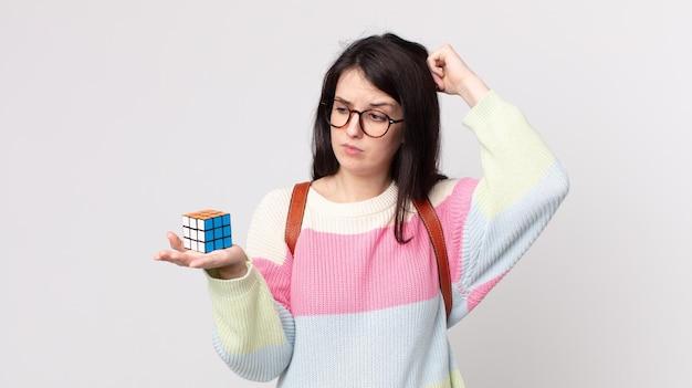 Mulher bonita se sentindo perplexa e confusa, coçando a cabeça e resolvendo um jogo de inteligência