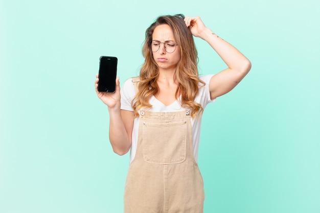 Mulher bonita se sentindo perplexa e confusa, coçando a cabeça e segurando um smartphone