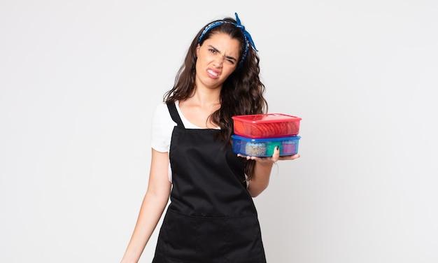 Mulher bonita se sentindo perplexa e confusa segurando tupperwares com comida