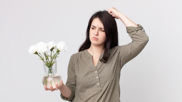 Mulher bonita se sentindo perplexo e confuso, coçando a cabeça e segurando flores decorativas. agente assistente com fone de ouvido