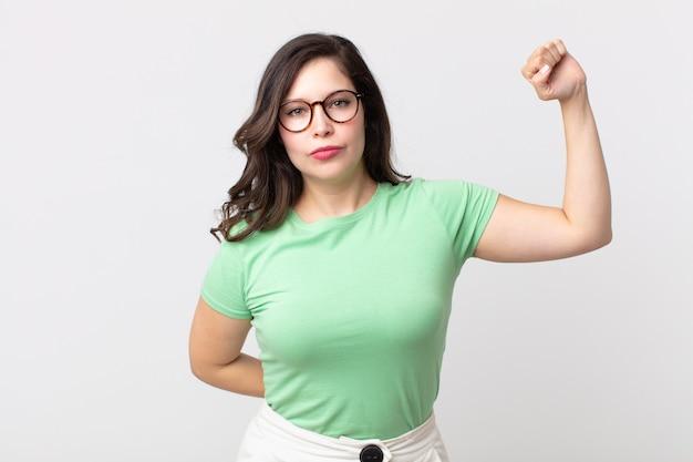 Mulher bonita se sentindo séria, forte e rebelde, levantando o punho, protestando ou lutando pela revolução