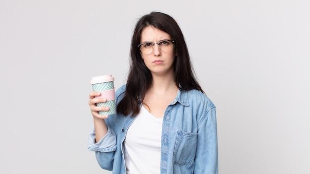 Mulher bonita se sentindo triste, chateada ou com raiva, olhando para o lado e segurando um café para viagem