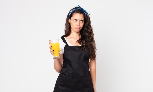 Mulher bonita se sentindo triste, chateada ou com raiva, olhando para o lado e segurando um copo de suco de laranja