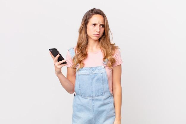 Mulher bonita se sentindo triste, chateada ou com raiva, olhando para o lado e segurando um smartphone