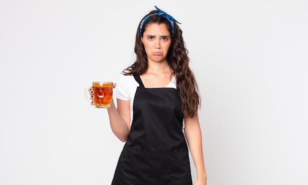 Mulher bonita se sentindo triste e chorona com um olhar infeliz, chorando e segurando um copo de cerveja