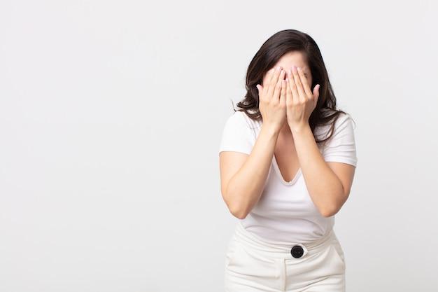 Mulher bonita se sentindo triste, frustrada, nervosa e deprimida, cobrindo o rosto com as duas mãos, chorando