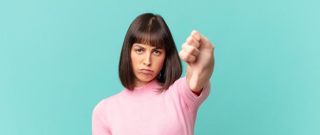 Mulher bonita se sentindo zangada, irritada, desapontada ou descontente, mostrando o polegar para baixo com um olhar sério
