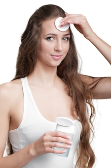 Mulher bonita segura almofada de algodão e tônica para remover a maquiagem. limpeza de pele
