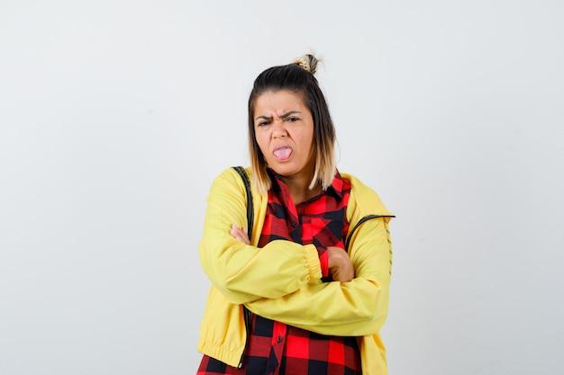 Mulher bonita, segurando os braços cruzados, mostrando a língua na camisa, jaqueta e parecendo enojado. vista frontal.