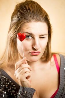 Mulher bonita segurando um coração vermelho decorativo e olhando para a câmera
