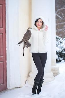 Mulher bonita segurando um falcão na mão no inverno