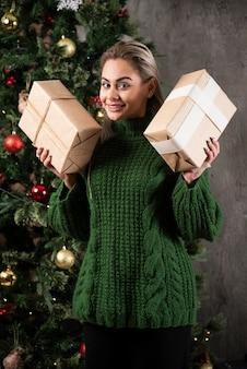 Mulher bonita segurando um presente de natal e ano novo perto de uma árvore de natal