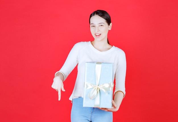 Mulher bonita segurando uma caixa de presente e o dedo indicador para baixo