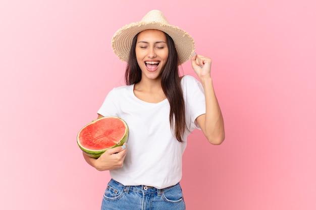 Mulher bonita segurando uma fatia de melancia