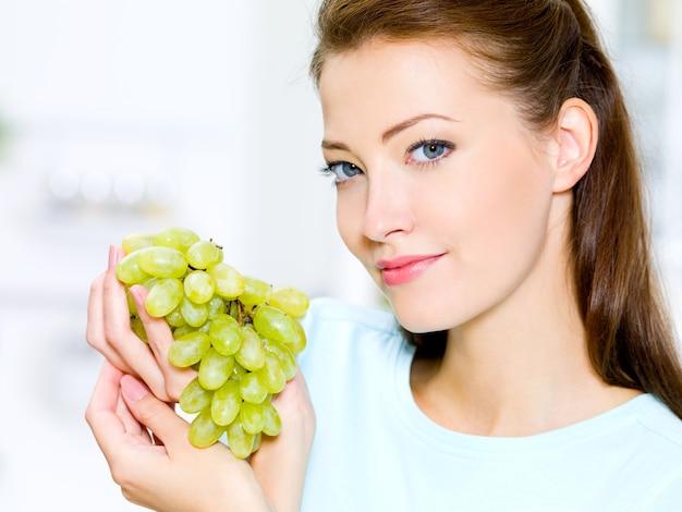 Mulher bonita segurando uvas - dentro de casa