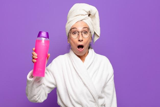 Mulher bonita sênior após o banho, vestindo um roupão de banho. conceito de produtos de limpeza ou banho facial