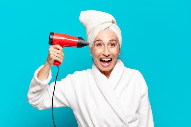 Mulher bonita sênior após o banho, vestindo um roupão de banho. conceito de secador de cabelo