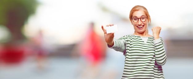 Mulher bonita sênior com um cartão de visita