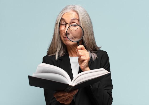 Mulher bonita sênior com um livro e uma lupa. conceito de pesquisa