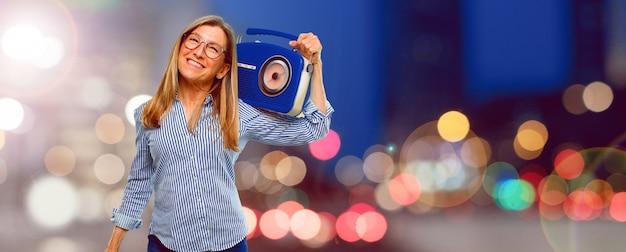 Mulher bonita sênior com um rádio vintage