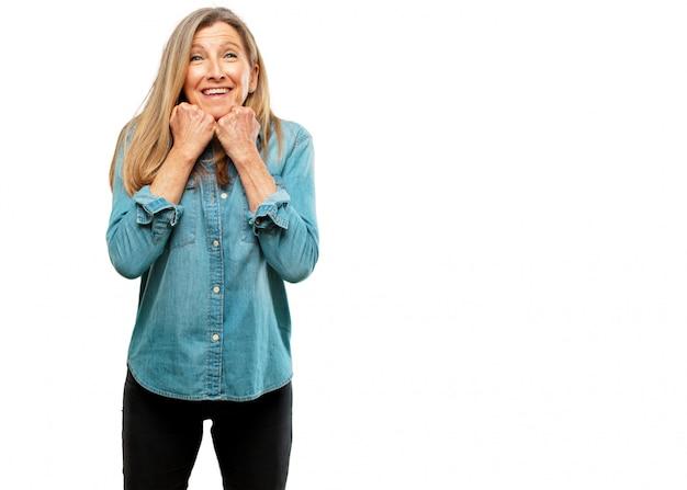 Mulher bonita sênior com uma expressão feliz surpresa, olhos bem abertos e largo sorriso, com ambos
