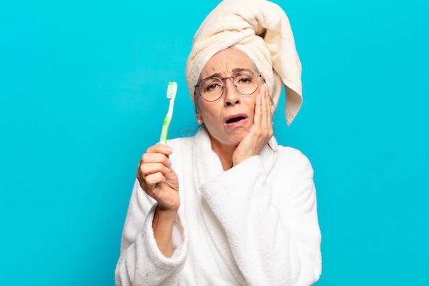 Mulher bonita sênior depois do banho de roupão e escova de dentes