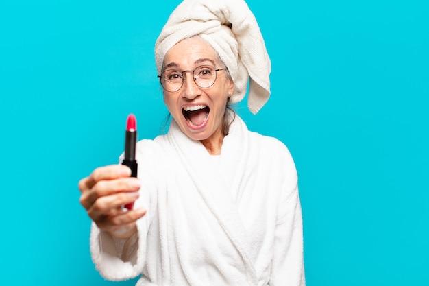 Mulher bonita sênior depois do banho se maquiando e vestindo roupão