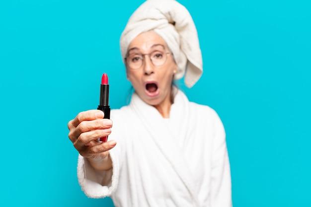 Mulher bonita sênior depois do banho se maquiando e vestindo um roupão de banho