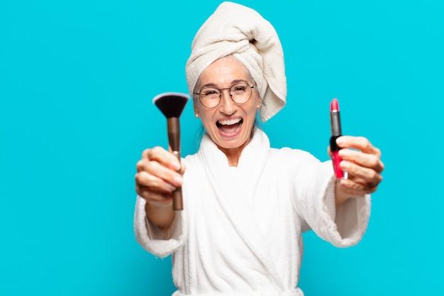 Mulher bonita sênior depois do banho, se maquiando e vestindo um roupão de banho