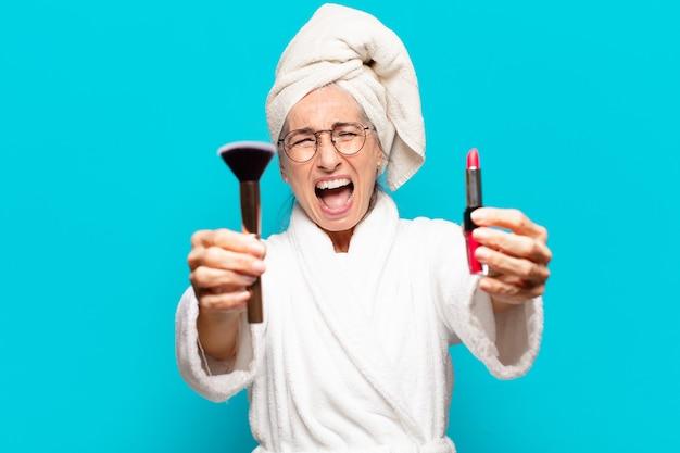 Mulher bonita sênior depois do banho, se maquiando e vestindo um roupão