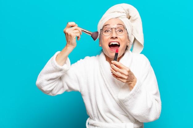 Mulher bonita sênior depois do banho se maquiando e vestindo um roupão