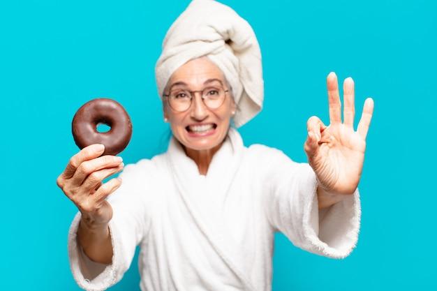 Mulher bonita sênior depois do banho, vestindo roupão de banho e tomando café da manhã com um donut