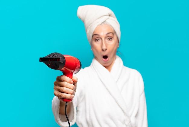Mulher bonita sênior depois do banho, vestindo um roupão de banho. conceito de secador de cabelo