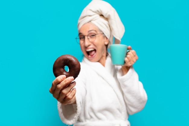Mulher bonita sênior depois do banho, vestindo um roupão de banho e tomando café da manhã com café e donut
