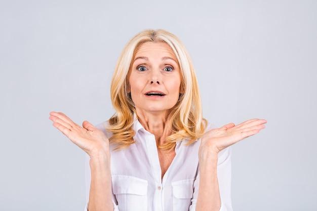 Mulher bonita sênior ou de meia-idade se sentindo chocada e animada, rindo, espantada e feliz por causa de uma surpresa inesperada isolada sobre fundo branco.